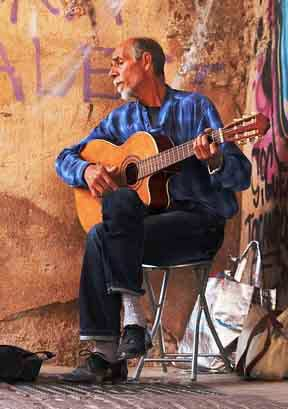 Guitarist-Playing-Cutaway-Classical-Guitar-in-Front-of-Graffiti-Wall