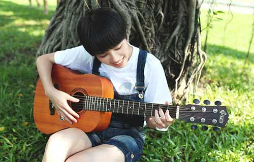 Young-Woman-Playing-Fingerstyle-on-Half-Size-Guitar