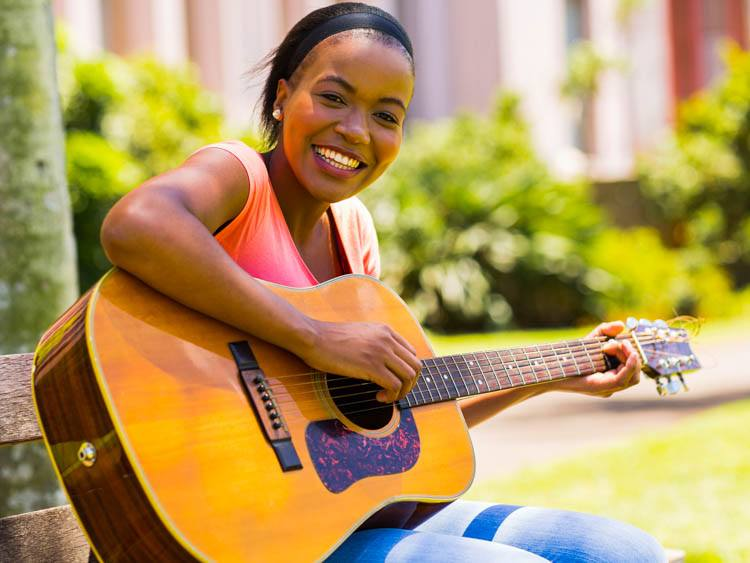 Young Woman Learning Guitar Onlie
