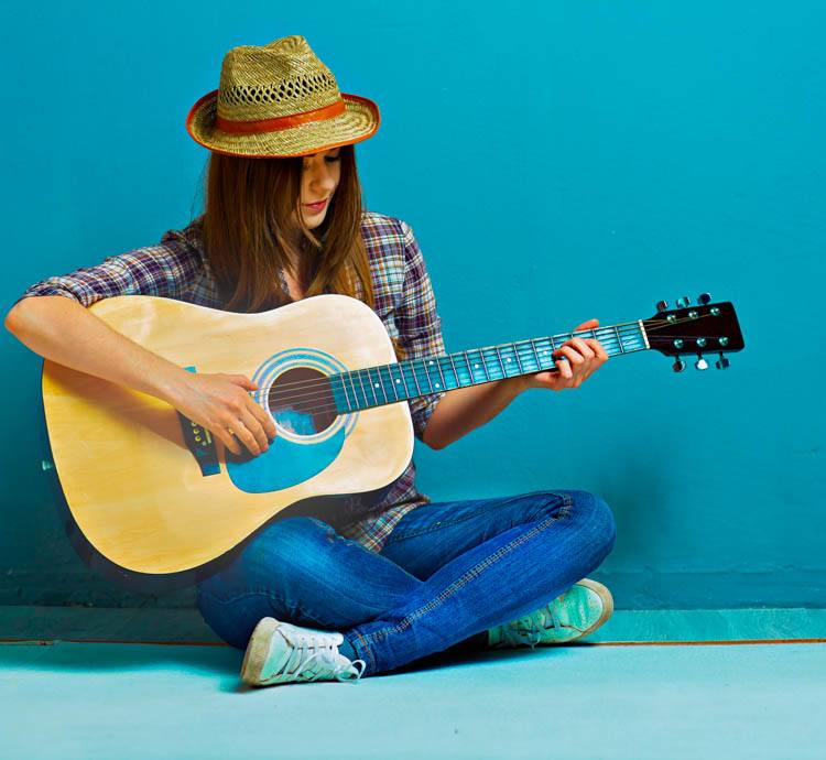 Young Woman with Hat Learning Guitar