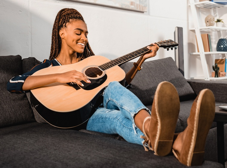 Woman with Braids Playing High Quality Guitar on Couch